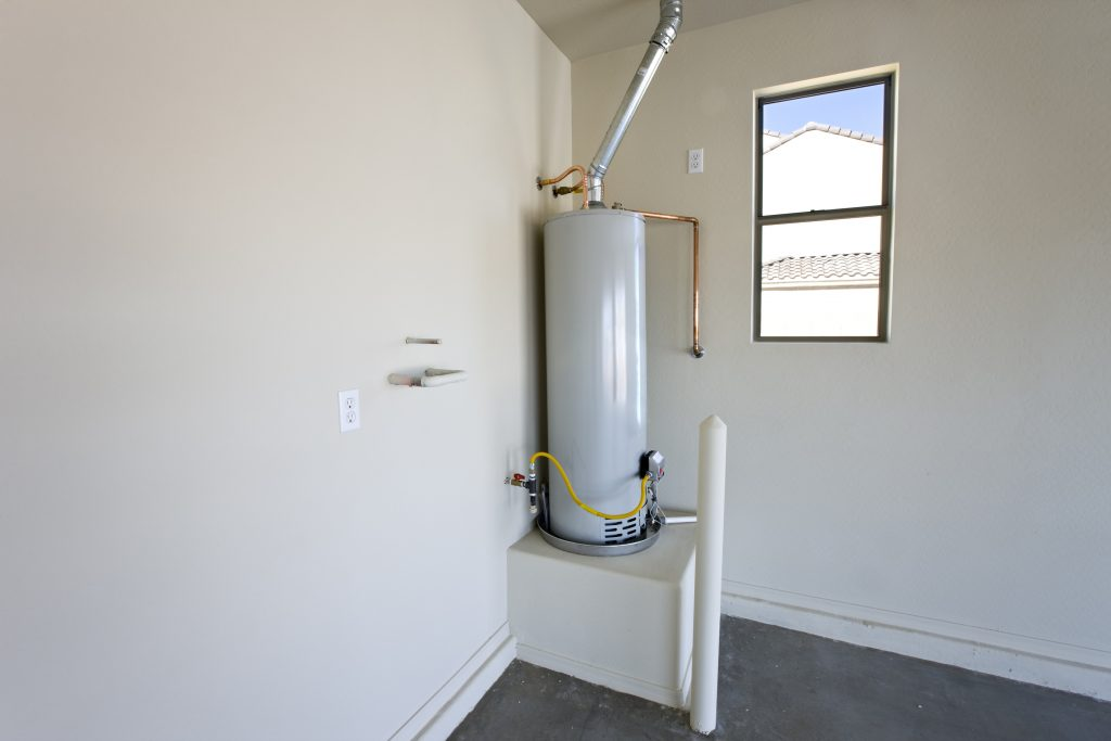 New hot water heater located in a clean and empty garage. Newly installed.
