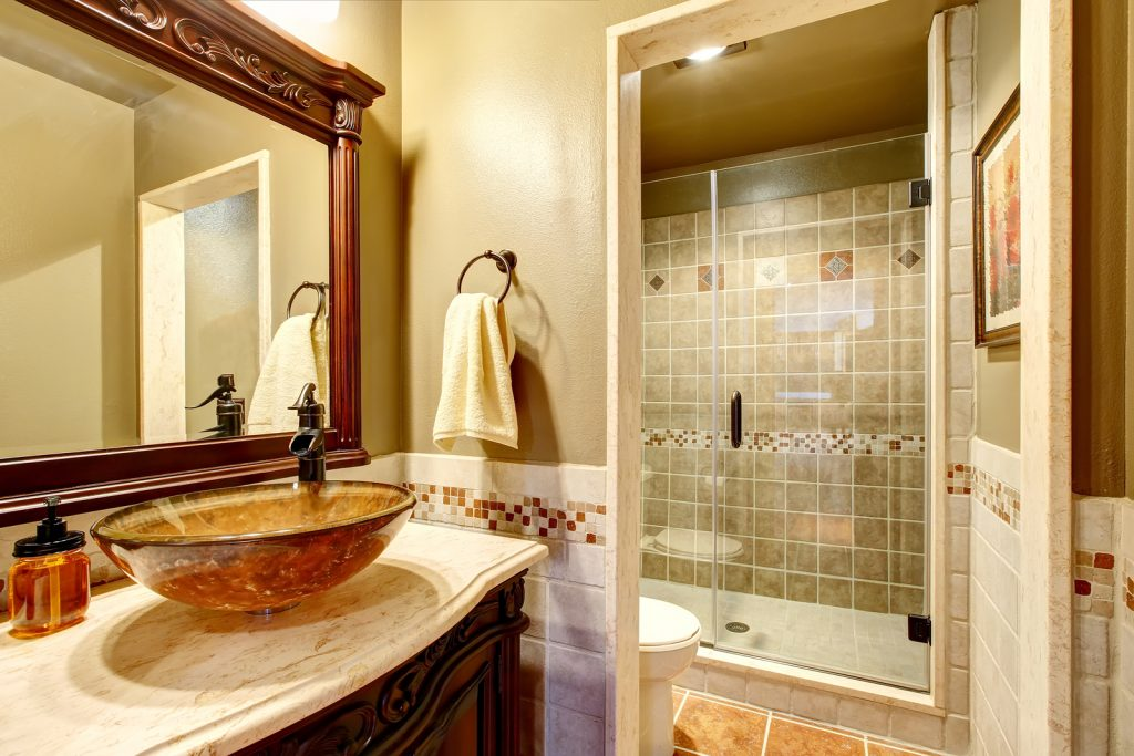 Bathroom interior in luxury house. Rich bathroom vanity cabinet with vessel sink and mirror. View of shower. Northwest USA